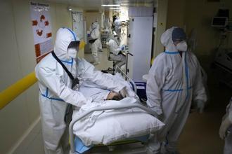 穿著特殊防護服的醫療人員正在運送新冠肺炎患者。俄羅斯當地疫情在本周二創下新高,對當地醫療系統造成嚴重負擔。(圖/美聯社)
